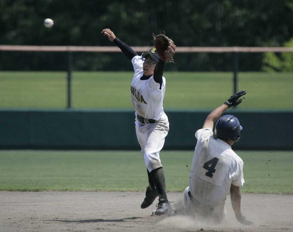【十和田西―東奥学園】8回、送りバントの処理で送球がそれるも、懸命に伸びて捕球する十和田西の遊撃手長畑純平(左)=メイプル